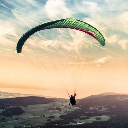 Parapente volando en el horizonte. 100% protegido con los seguros de viaje Ponce y Mugar