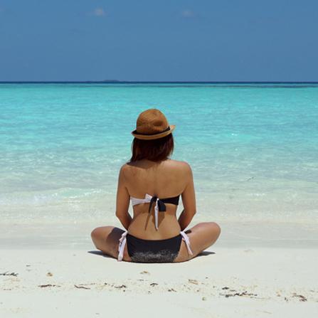 Mujer de espaldas en la playa disfrutando del seguro de viaje Esencial de Ponce y Mugar